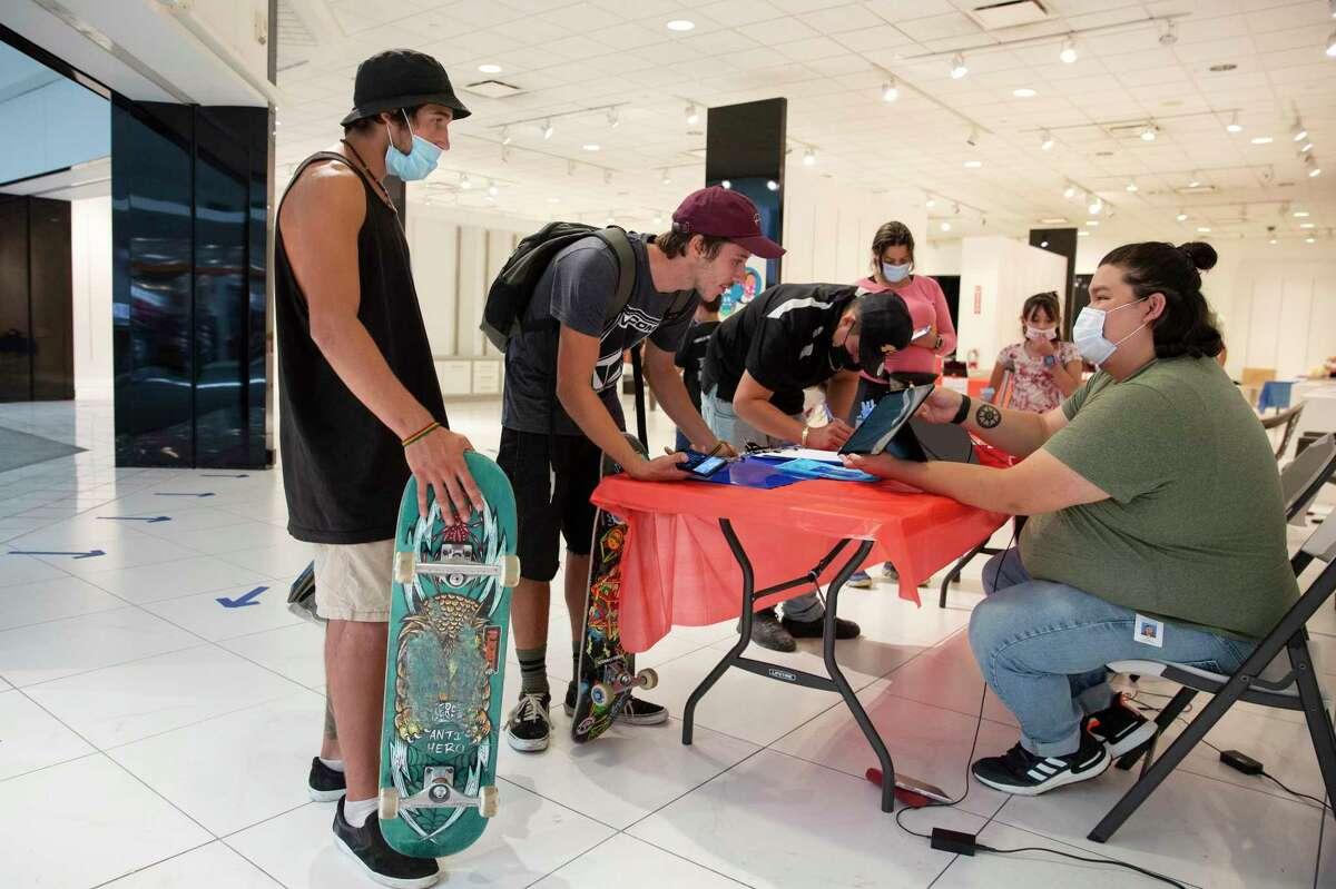 Franch Agustin (izquierda) y Santiago Gyurzi puntúan con Max Headley, un pasante del Departamento de Salud Pública del Condado de Solano, antes de recibir las vacunas COVID-19 en Solano Town Center Mall en Fairfield.