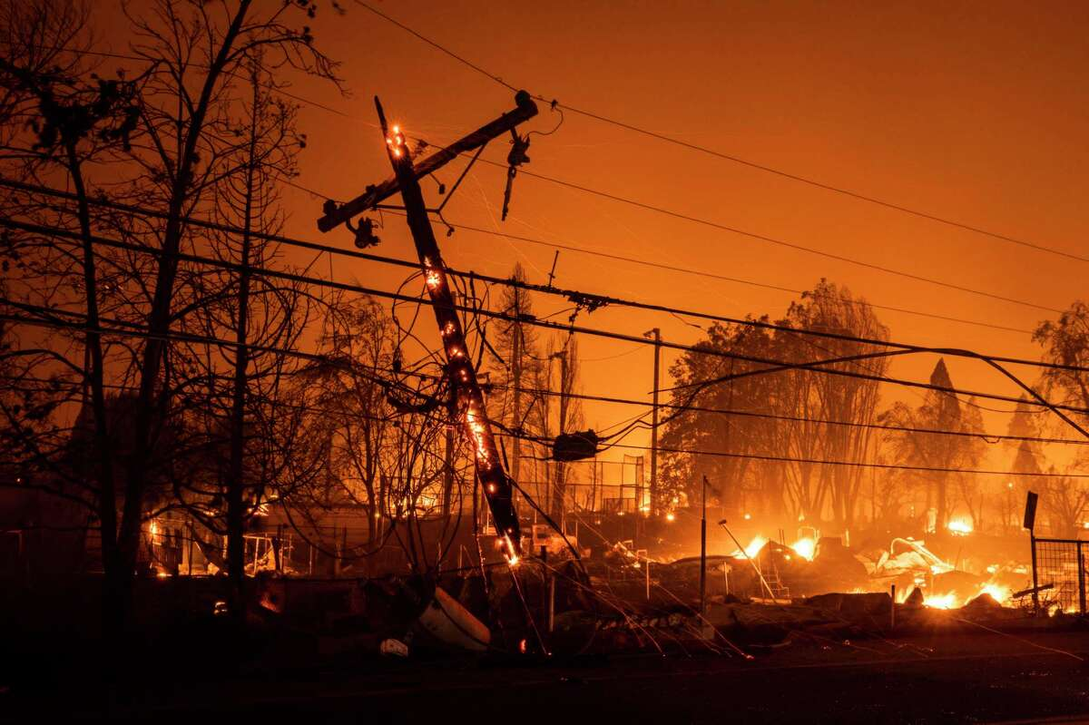 A utility pole smolders as the Dixie Fire burns through last week.