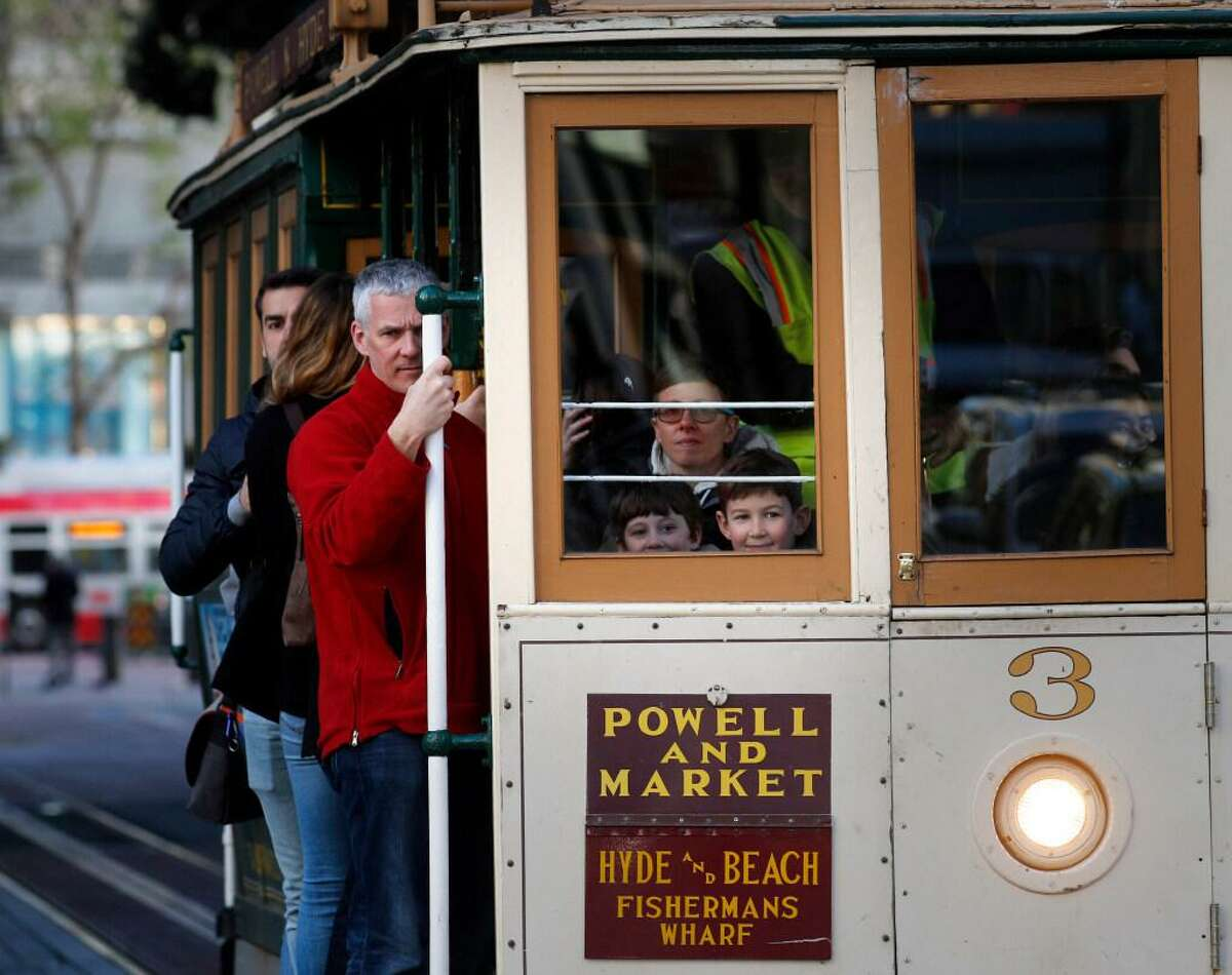 Families ride the world famous cable cars along the Powell st. line in San Francisco, Calif. on Mon. Mar. 26, 2018.