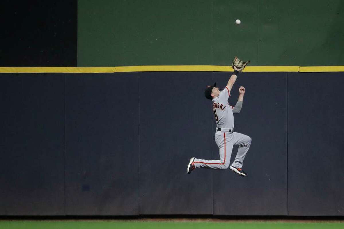 San Francisco Giants' Mike Yastrzemski makes a leaping catch at the wall on a ball hit by Milwaukee Brewers' Rowdy Tellez during the fourth inning of a baseball game Friday, Aug. 6, 2021, in Milwaukee. (AP Photo/Aaron Gash)