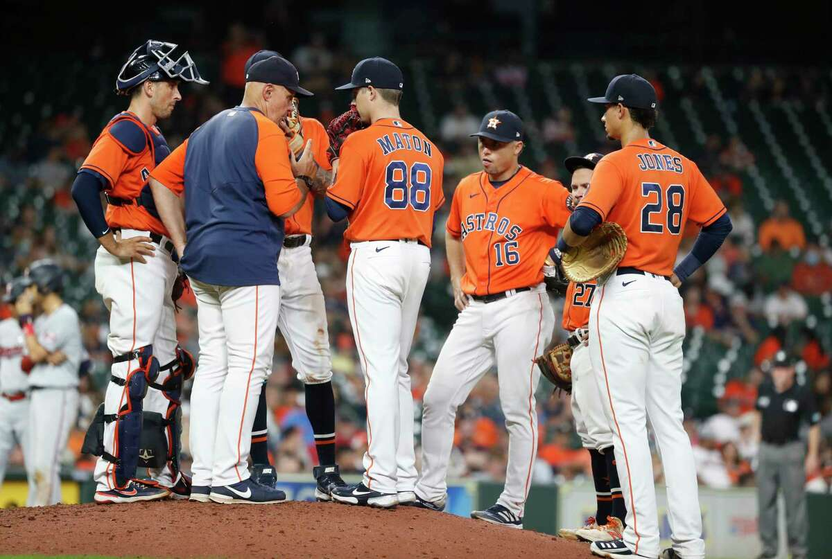 Houston Astros pitching coach Brent Strom (56) talks with relief pitcher Phil Maton (88) during the tenth inning of an MLB baseball game at Minute Maid Park, Friday, August 6, 2021, in Houston.