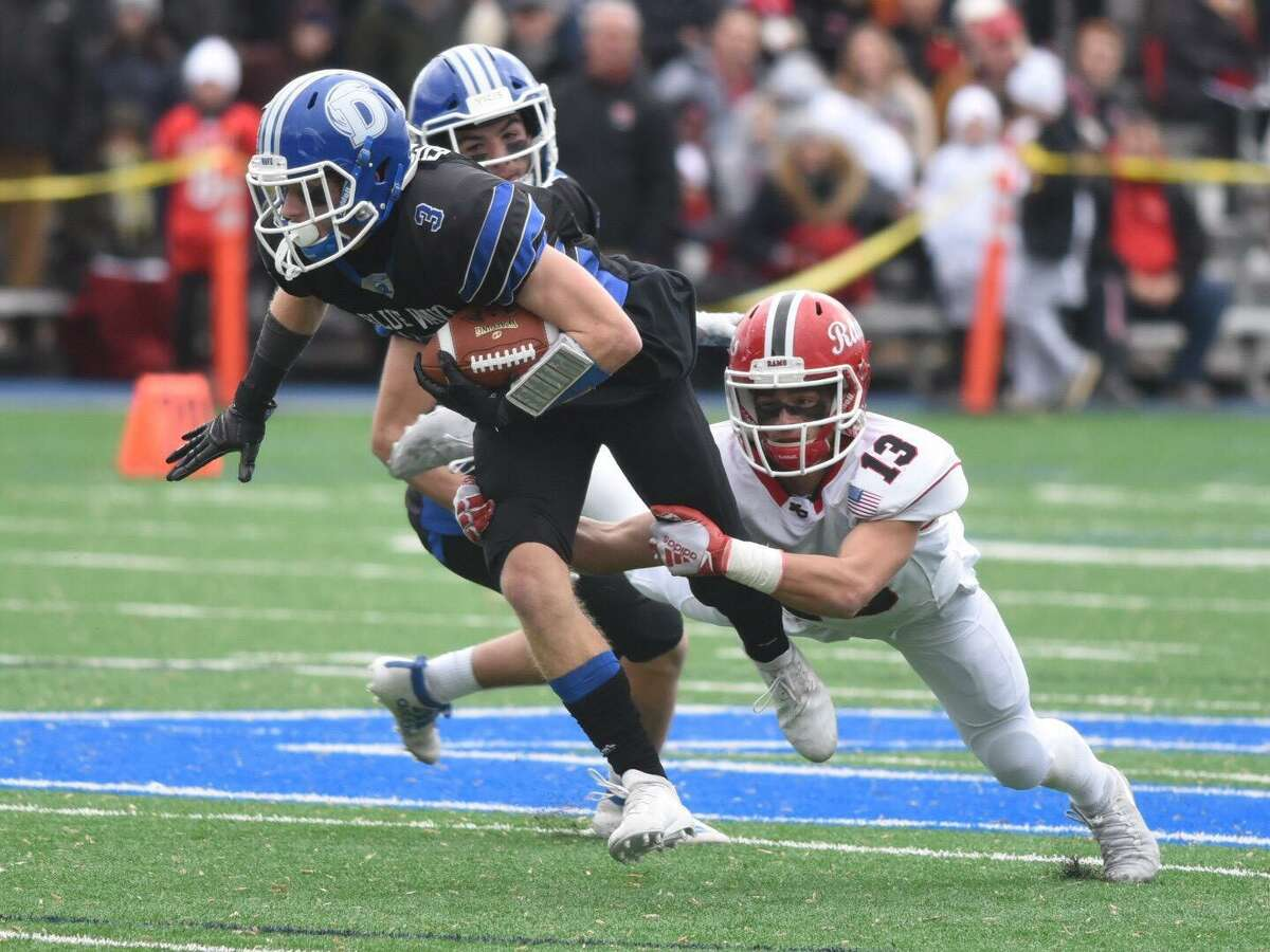New Canaan's Walker Swindell (13) tackles Darien's Sean Gifford (3) after a catch during the annual Turkey Bowl at Darien High in 2019.