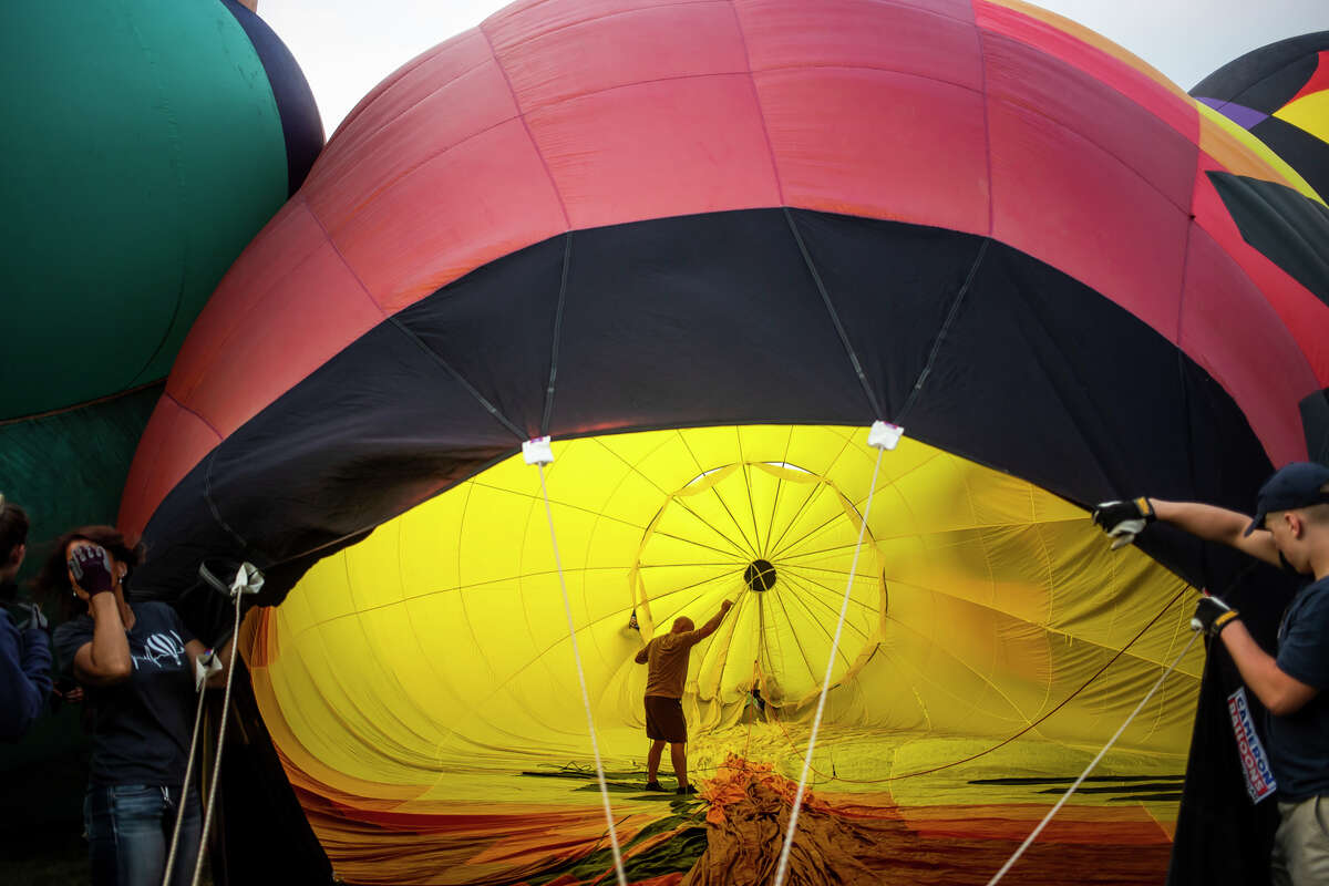 Hot air balloon pilot Scott Strouse, center, prepares to take off from Chippewassee Park for a leisurely flight during the River Days Festival and Midland Balloon Fest Friday, Aug. 6, 2021. (Katy Kildee/kkildee@mdn.net)