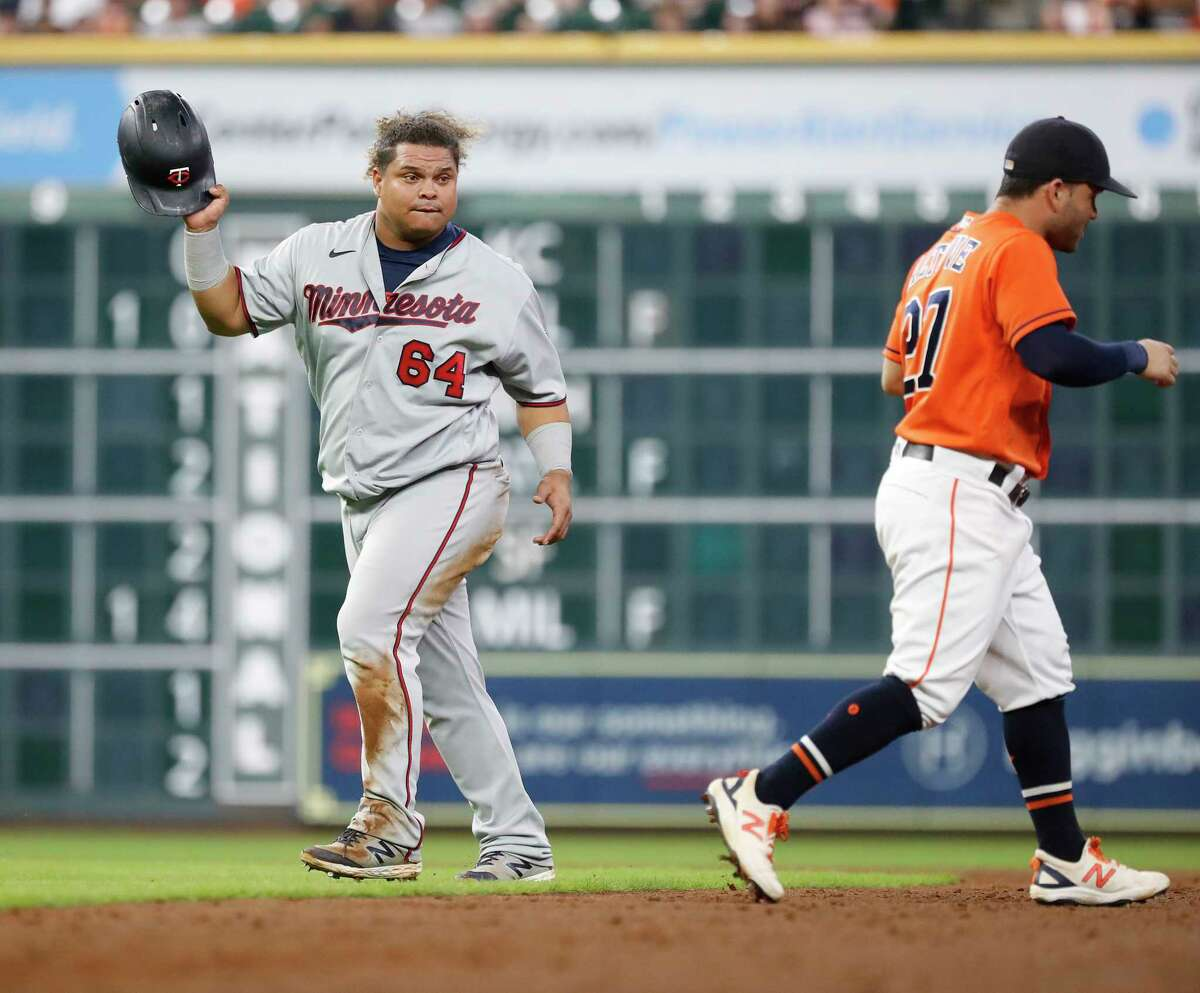 Minnesota Twins Willians Astudillo (64) acts like he was going to throw his batting helmet at Houston Astros second baseman Jose Altuve (27) after he tagged him out during the eleventh inning of an MLB baseball game at Minute Maid Park, Friday, August 6, 2021, in Houston.