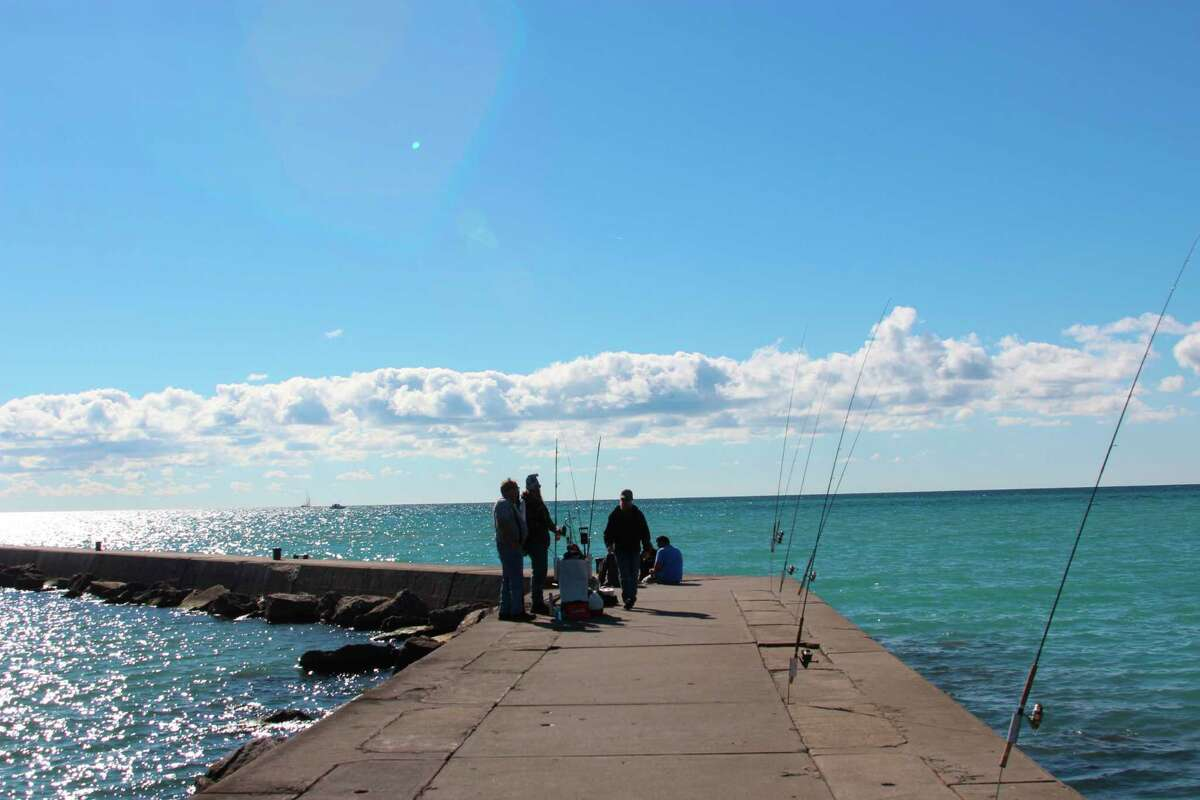 Anglers fish off the pier at Frankfort when the water starts to cool down and salmon come in closer to prepare for their spawning run up the Betsie River. (File Photo)
