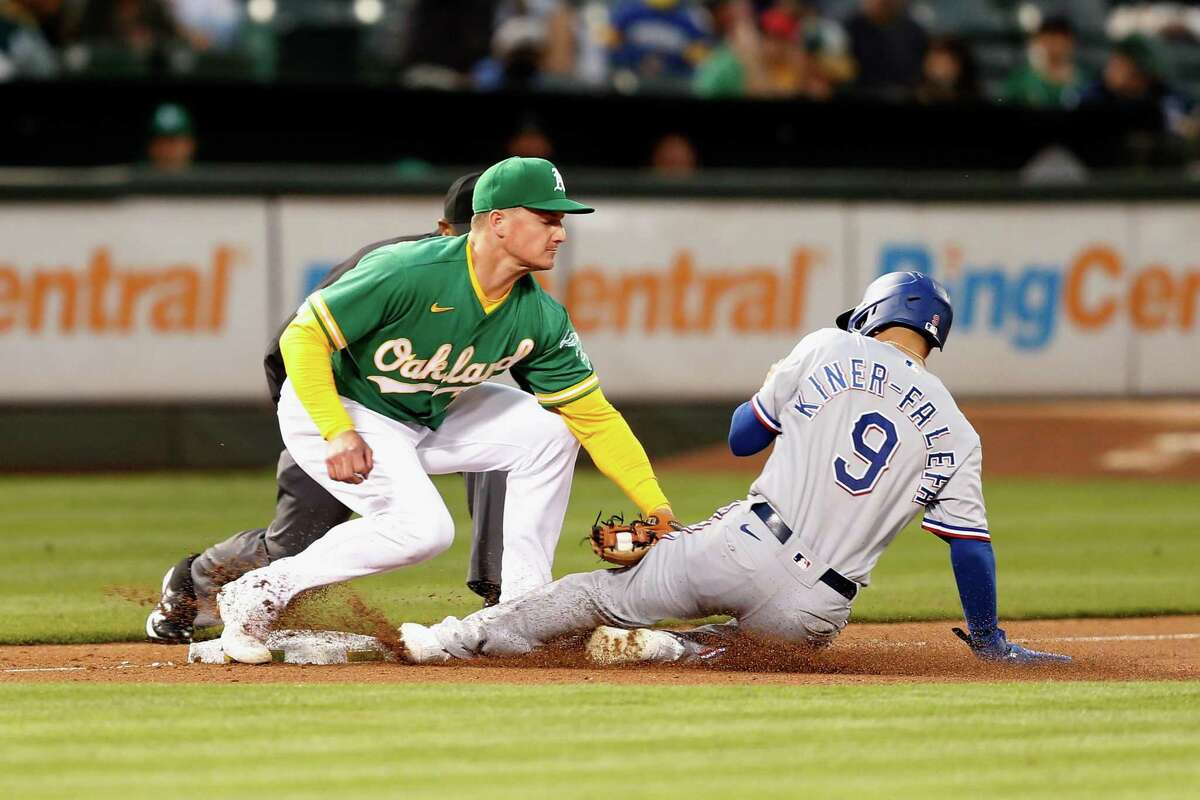 OAKLAND, CALIFORNIA - AUGUST 06: Isiah Kiner-Falefa #9 of the Texas Rangers is tagged out by Matt Chapman #26 of the Oakland Athletics while trying to steal third base in the top of the fifth inning at RingCentral Coliseum on August 06, 2021 in Oakland, California. (Photo by Lachlan Cunningham/Getty Images)