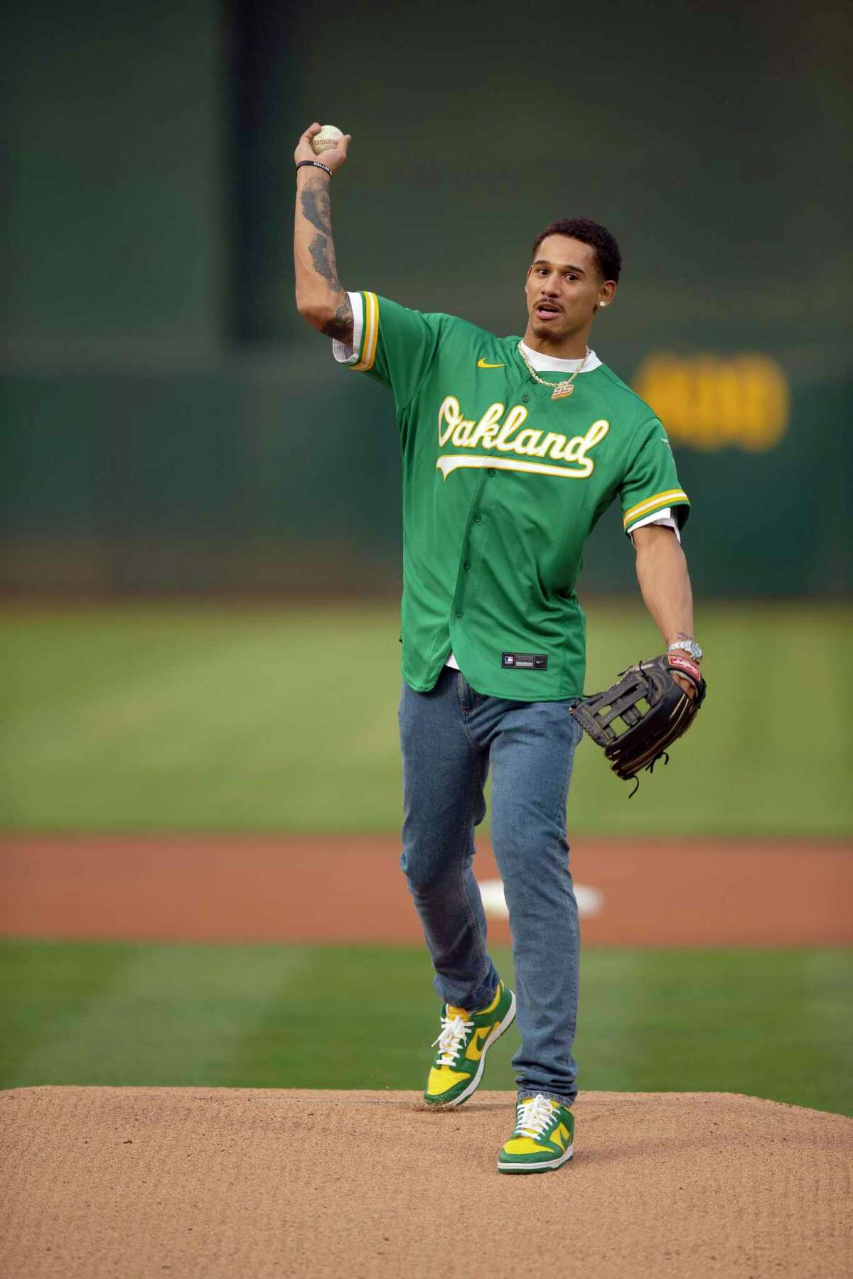 Golden State Warriors forward Juan Toscano Anderson throws the first pitch before a baseball game between the Oakland Athletics and the Texas Rangers, Friday, Aug. 6, 2021, in Oakland, Calif. (AP Photo/D. Ross Cameron)
