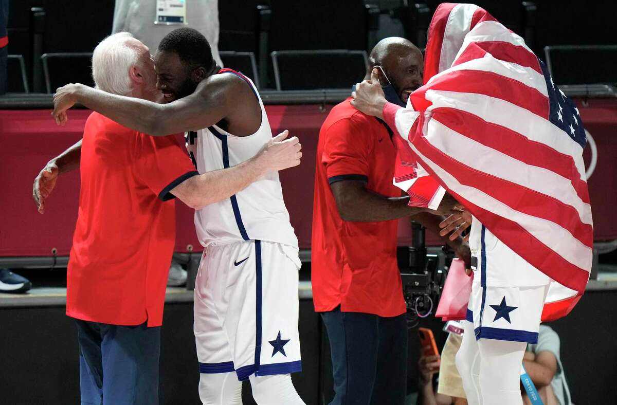 United States' Draymond Green (14), second left, hugs head coach Gregg Popovich to celebrate after their win in the men's basketball gold medal game against France at the 2020 Summer Olympics, Saturday, Aug. 7, 2021, in Saitama, Japan. (AP Photo/Luca Bruno)
