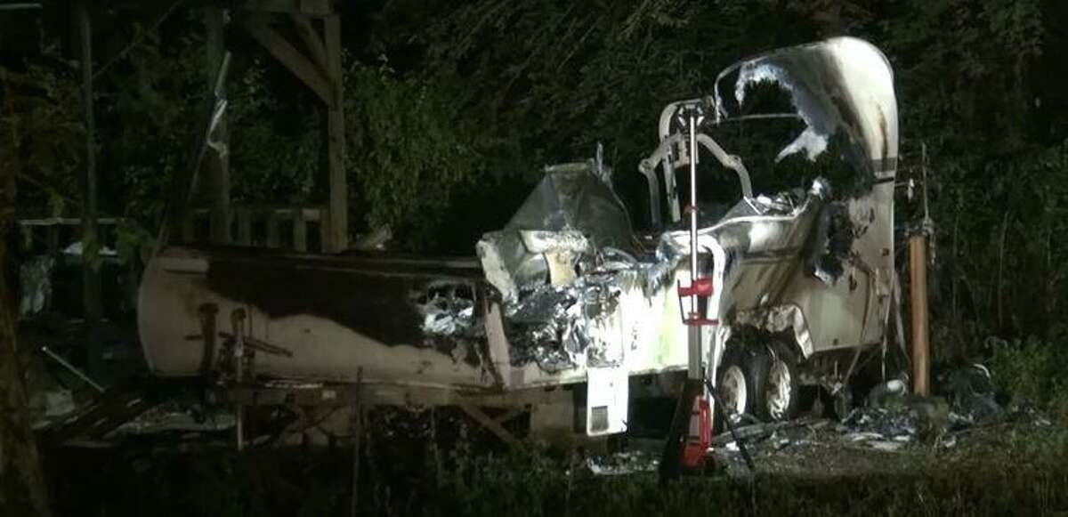 A charred recreational vehicle is seen at a New Caney address after fire consumed it, killing its occupant.