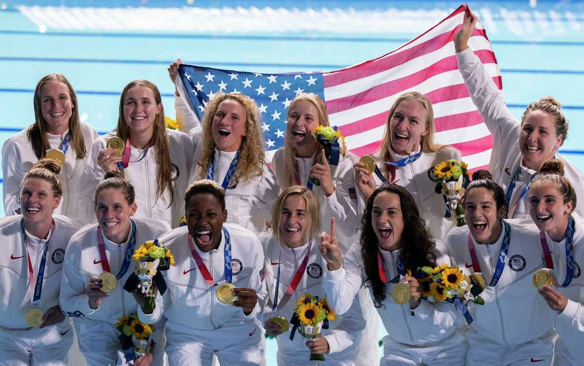 The U.S. women's water polo team poses with their gold medals after defeating Spain at the 2020 Summer Olympics, in Tokyo, on Saturday, Aug. 7, 2021. (Alexandra Garcia/The New York Times)