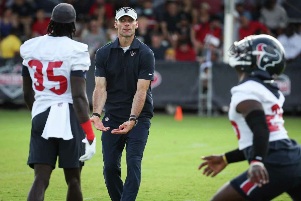Houston Texans general manager Nick Caserio works with defensive back Keion Crossen (35) during an NFL training camp football practice Monday, Aug. 2, 2021, in Houston.