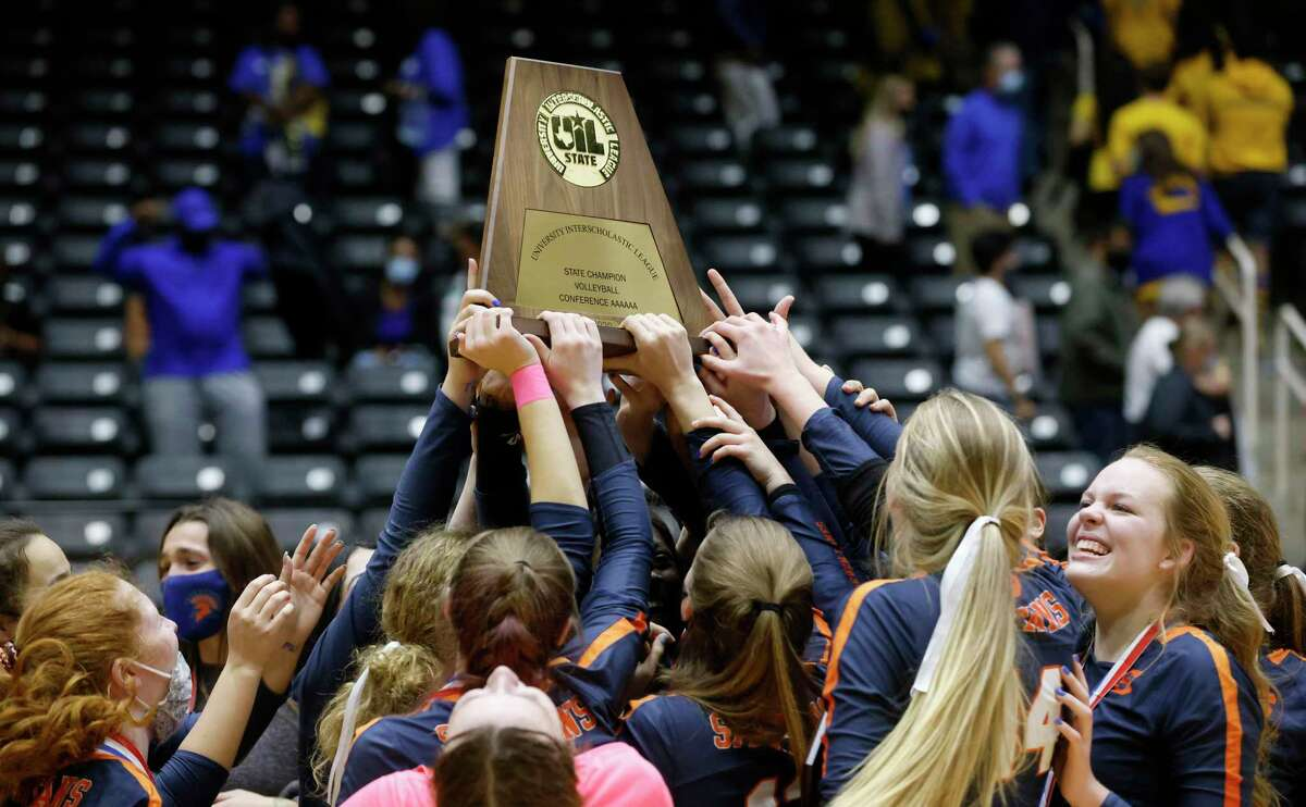 Seven Lakes team members, including Casey Batenhorst (right) reach or the championship trophy after defeating Klein in the Conference 6A State High School volleyball championship in Garland, Texas on Dec. 12, 2020. (Michael Ainsworth/ Contributor)