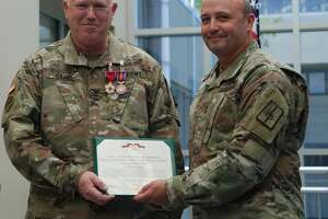Col. Jim Cahill, left, receives a Legion of Merit citation from Maj. Gen. Michel Natali, assistant adjutant general of the New York National Guard, in Latham.