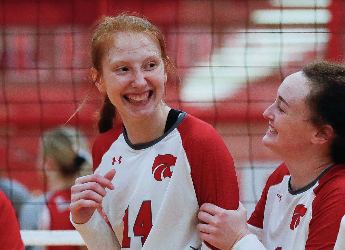 Splendora middle blocker Jalynn Knight, center, gets a hug from setter Falton Buford after scoring the match point to win the fifth set of a non-district high school volleyball match at Splendora High School, Tuesday, Aug. 18, 2020, in Splendora.