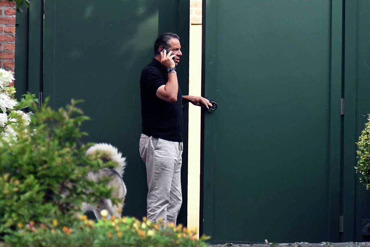 Gov. Andrew Cuomo talks on the phone while walking with his dog Captain at the New York state Executive Mansion, Saturday, Aug. 7, 2021, in Albany, N.Y. An investigation found that Cuomo sexually harassed multiple women in and out of state government. (AP Photo/Hans Pennink)