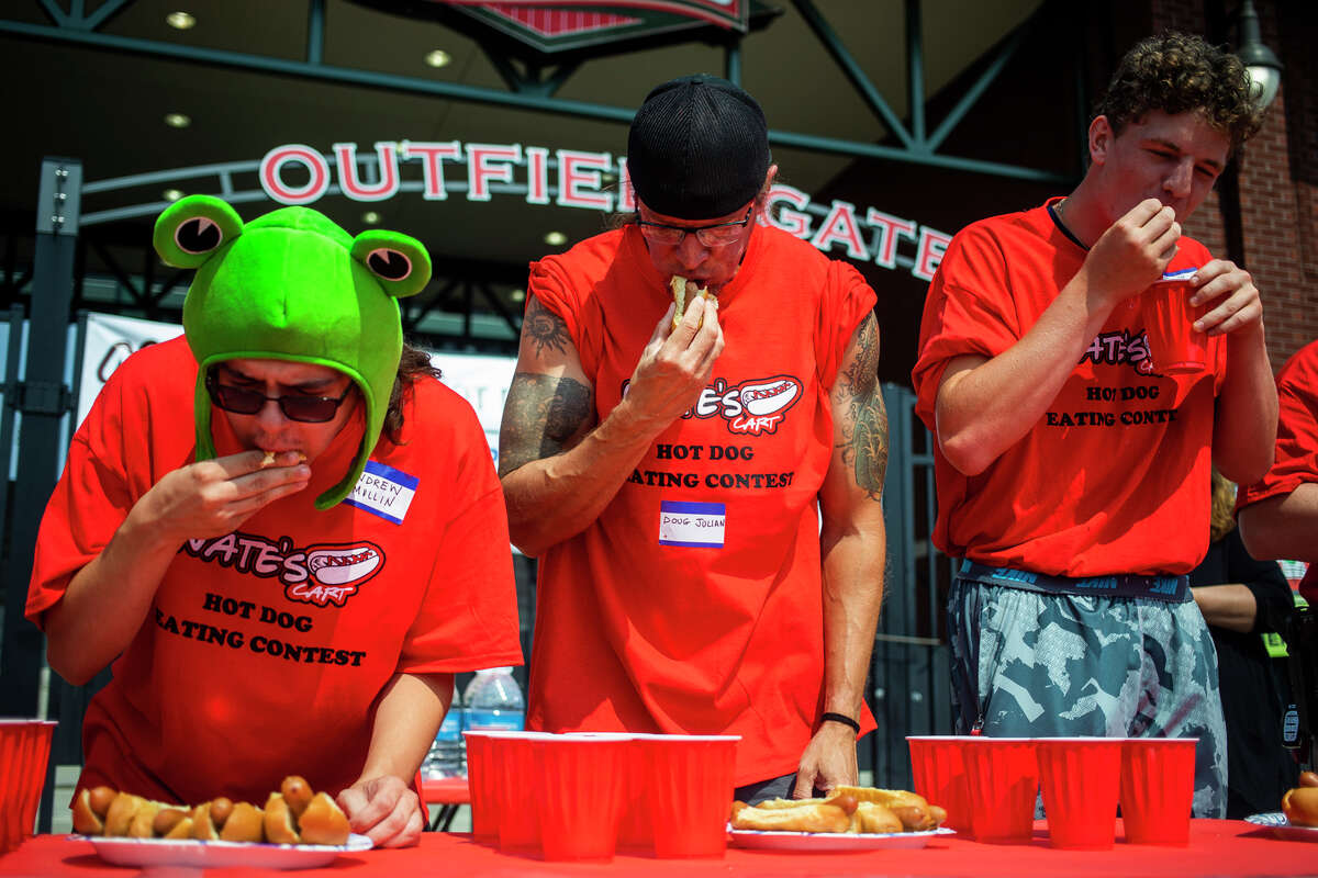 From left, Andrew Mullin, Doug Julian and Danny Terburgh compete in a hot dog eating contest hosted by Nate's Cart Saturday, Aug. 7, 2021 at the Midland Area Farmers Market at Dow Diamond. (Katy Kildee/kkildee@mdn.net)