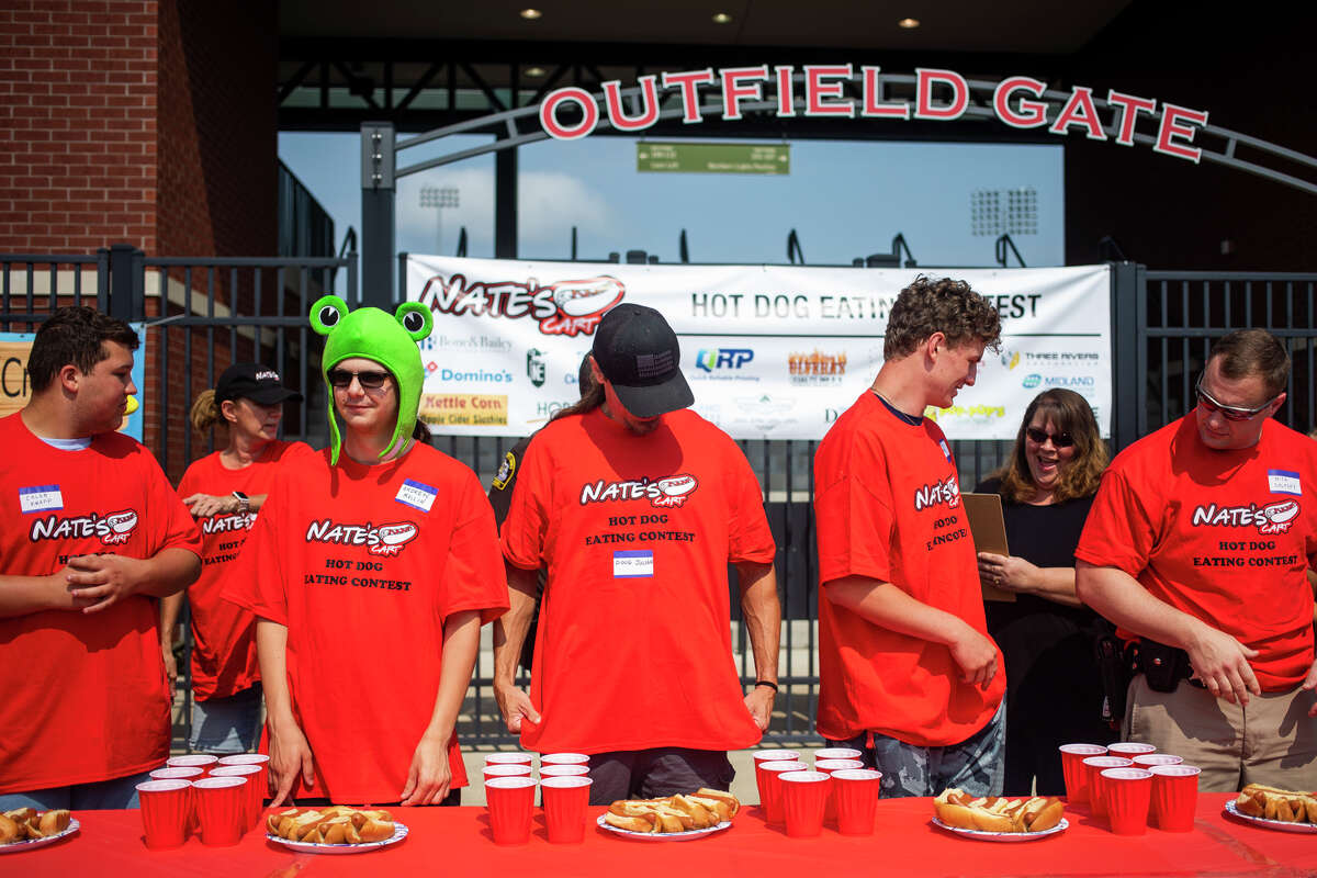 From left, Caleb Knapp, Andrew Mullin, Doug Julian, Danny Terburgh and Nick Solosky prepare to compete in a hot dog eating contest hosted by Nate's Cart Saturday, Aug. 7, 2021 at the Midland Area Farmers Market at Dow Diamond. (Katy Kildee/kkildee@mdn.net)