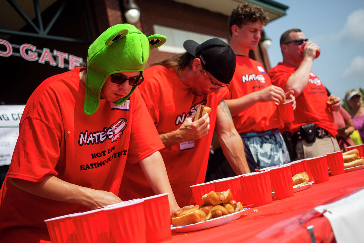 From left, Andrew Mullin, Doug Julian, Danny Terburgh and Nick Solosky compete in a hot dog eating contest hosted by Nate's Cart Saturday, Aug. 7, 2021 at the Midland Area Farmers Market at Dow Diamond. (Katy Kildee/kkildee@mdn.net)
