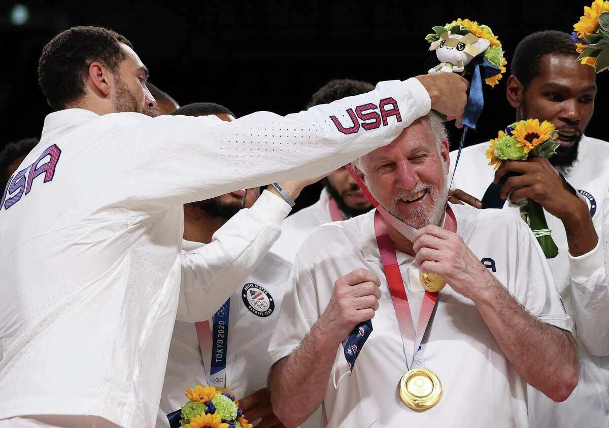 SAITAMA, JAPAN - AUGUST 07: Zachary Lavine presents Team United States Head Coach Gregg Popovich with his gold medal during the Men's Basketball medal ceremony on day fifteen of the Tokyo 2020 Olympic Games at Saitama Super Arena on August 07, 2021 in Saitama, Japan. (Photo by Gregory Shamus/Getty Images)