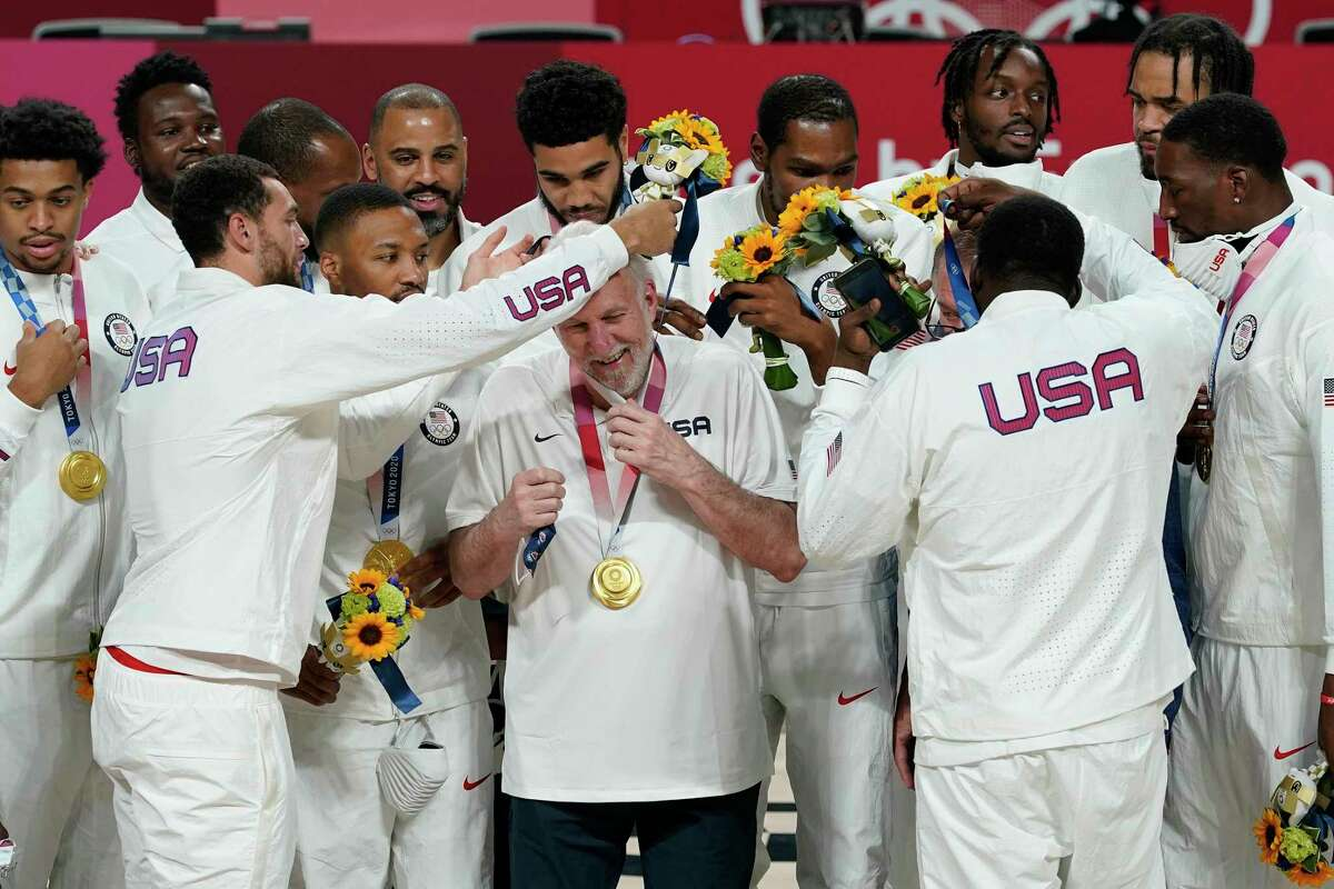 U.S. players put a gold medal on each coach Gregg Popovich during the men's basketball medal ceremony at the 2020 Summer Olympics, Saturday, Aug. 7, 2021, in Tokyo, Japan. (AP Photo/Charlie Neibergall)