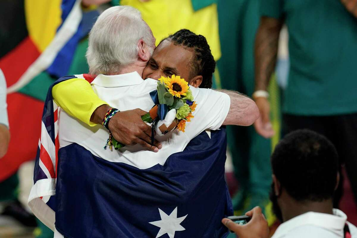 Australia's Patty Mills (5) hugs U.S. coach Gregg Popovich during the medal ceremony for basketball game at the 2020 Summer Olympics, Saturday, Aug. 7, 2021, in Tokyo, Japan. (AP Photo/Charlie Neibergall)