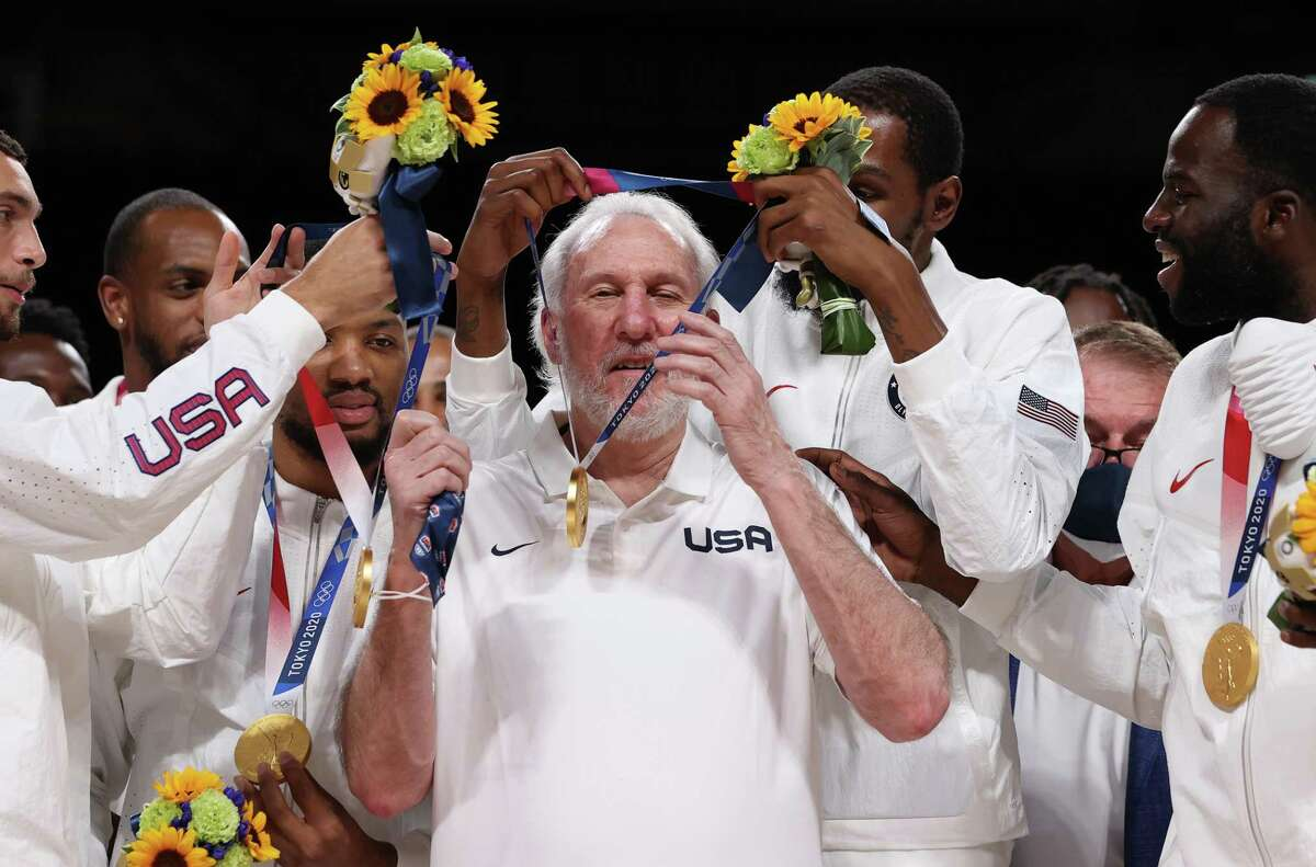 Kevin Durant of Team USA presents head coach Gregg Popovich with his gold medal during the men's basketball medal ceremony at the Tokyo 2020 Olympic Games at Saitama Super Arena on August 07, 2021 in Saitama, Japan.