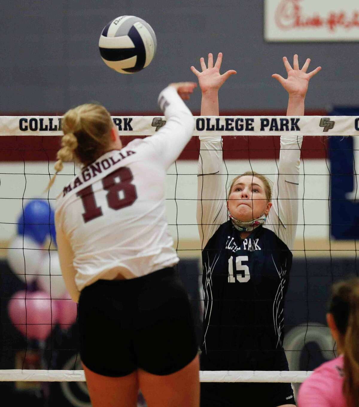 College Park's Paige Bernstein (15) pressures a shot by Magnolia's Brynn Botkin (18) during the first set of a non-district high school volleyball match at College Park High School, Saturday, Sept. 26, 2020, in The Woodlands.