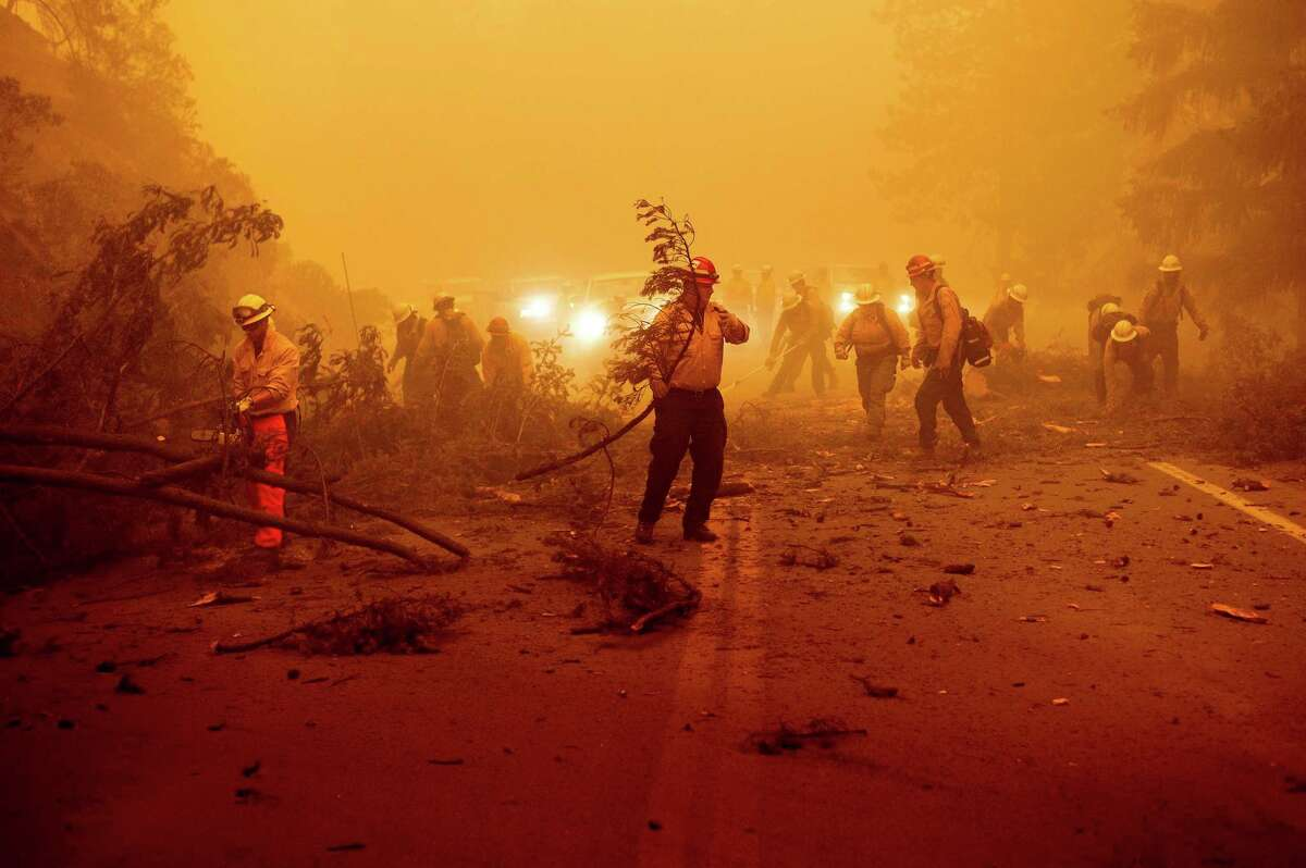 Firefighters battling the Dixie Fire clear Highway 89 after a burned tree fell across the roadway in Plumas County on Friday.