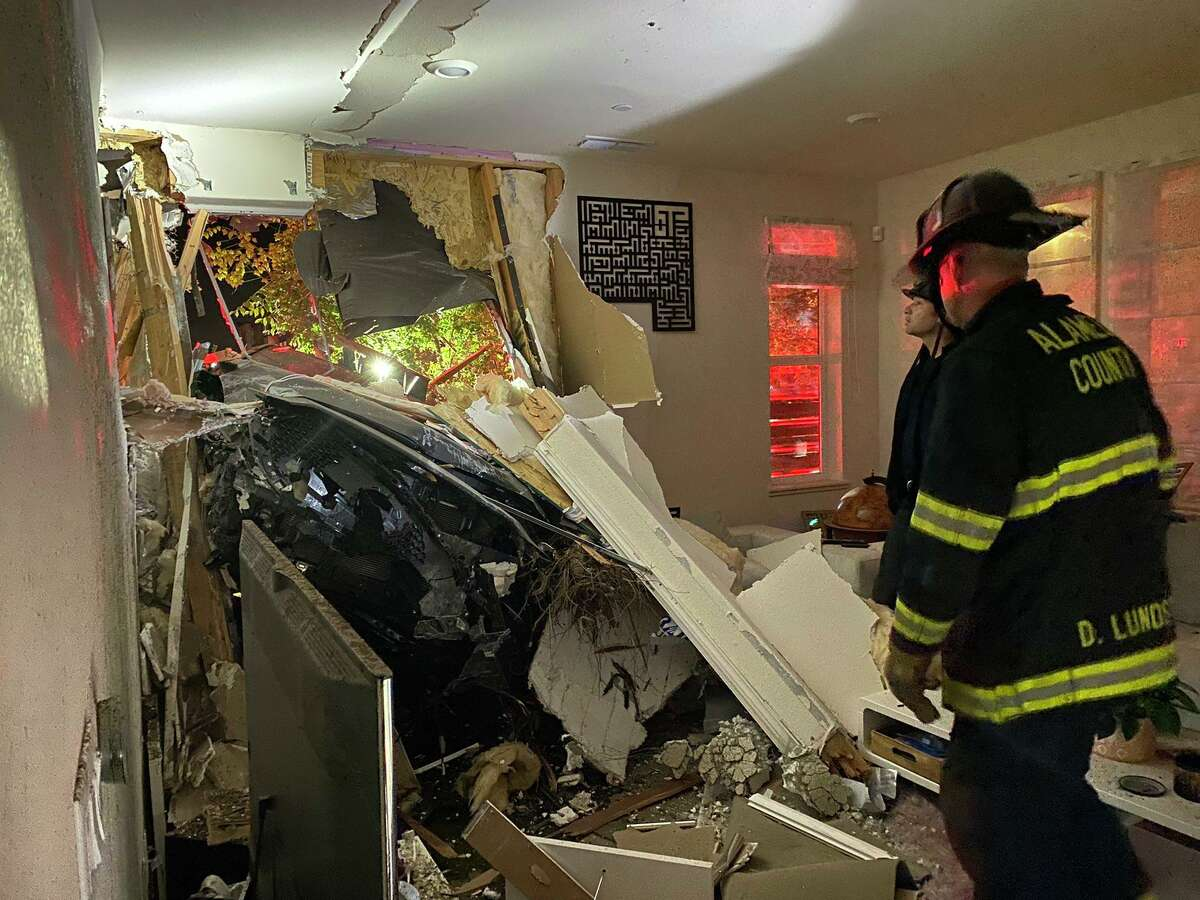 Alameda County firefighters survey the property damage inside a Dublin home on Saturday, Aug. 7, 2021, when a blue Mazda Hatchback crashed early in the morning.
