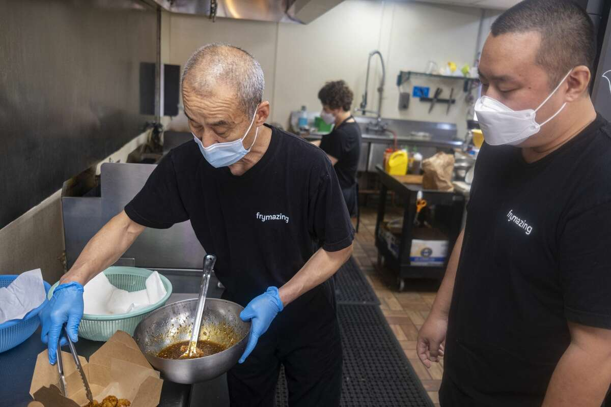 Yuh Il Yoon and son Tae Yoon make a chicken dish at Frymazing.