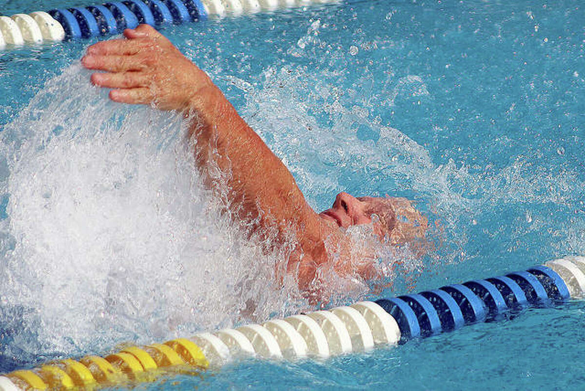 Recently retired Marquette Catholic High School principal Mike Slaughter, 65, competes in the backstroke during the 100-yard medley relay Saturday at the first Summers Port alumni swim meet in Godfrey. The event was a fundraiser for the Summers Port Sharks swim team.
