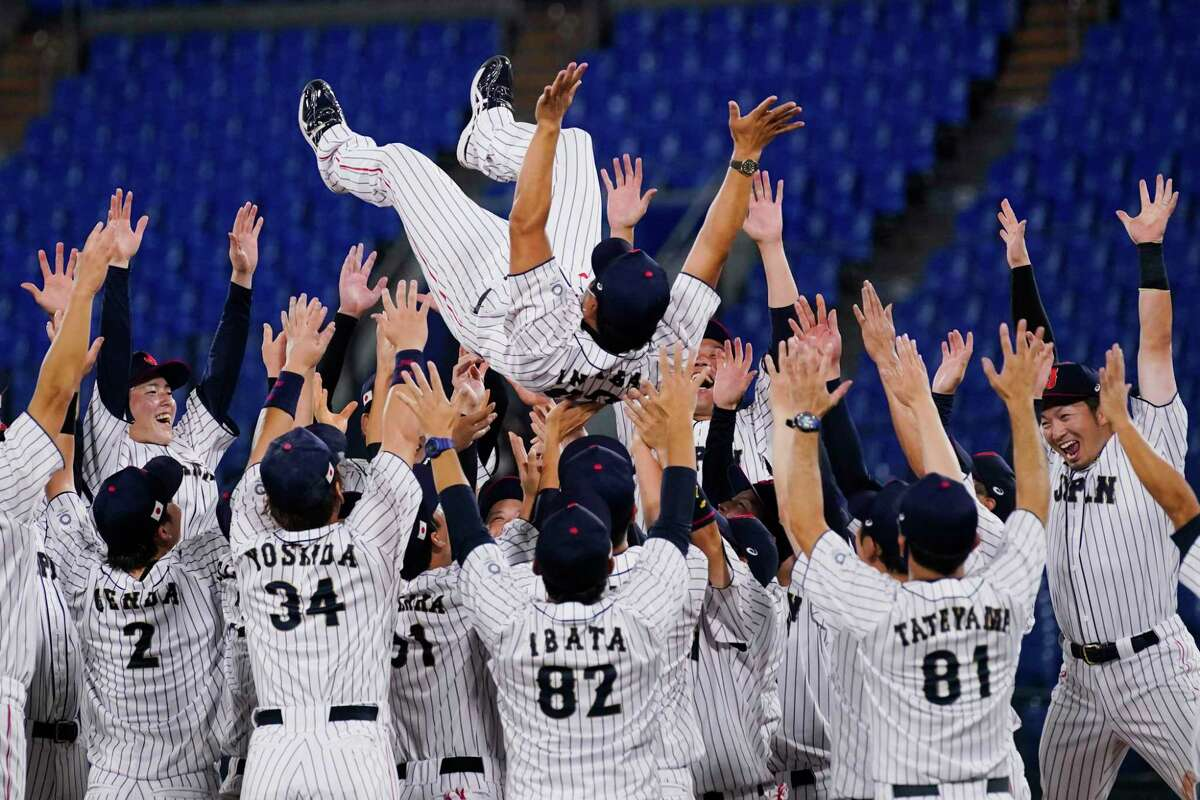 Team Japan celebrate with their manager Atsunori Inaba after the gold medal baseball game against the United States.
