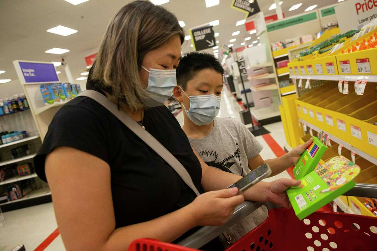 Pearl Lee and son Simeon shop for supplies, to prepare for in-person classes to resume soon with a new semester, during the tax-free weekend Saturday at Memorial City Mall.