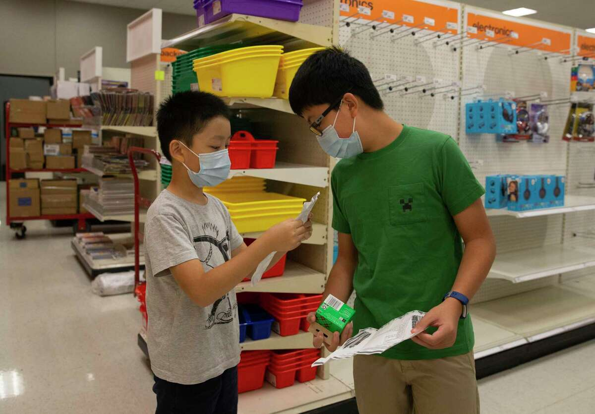 Simeon Lee, left, asks his brother, Quenton Lee, help him locate pencil while their family is shopping for school supplies to prepare for new semester at Target during the tax-free weekend Saturday, Aug. 7, 2021, at Memorial City Mall in Houston.