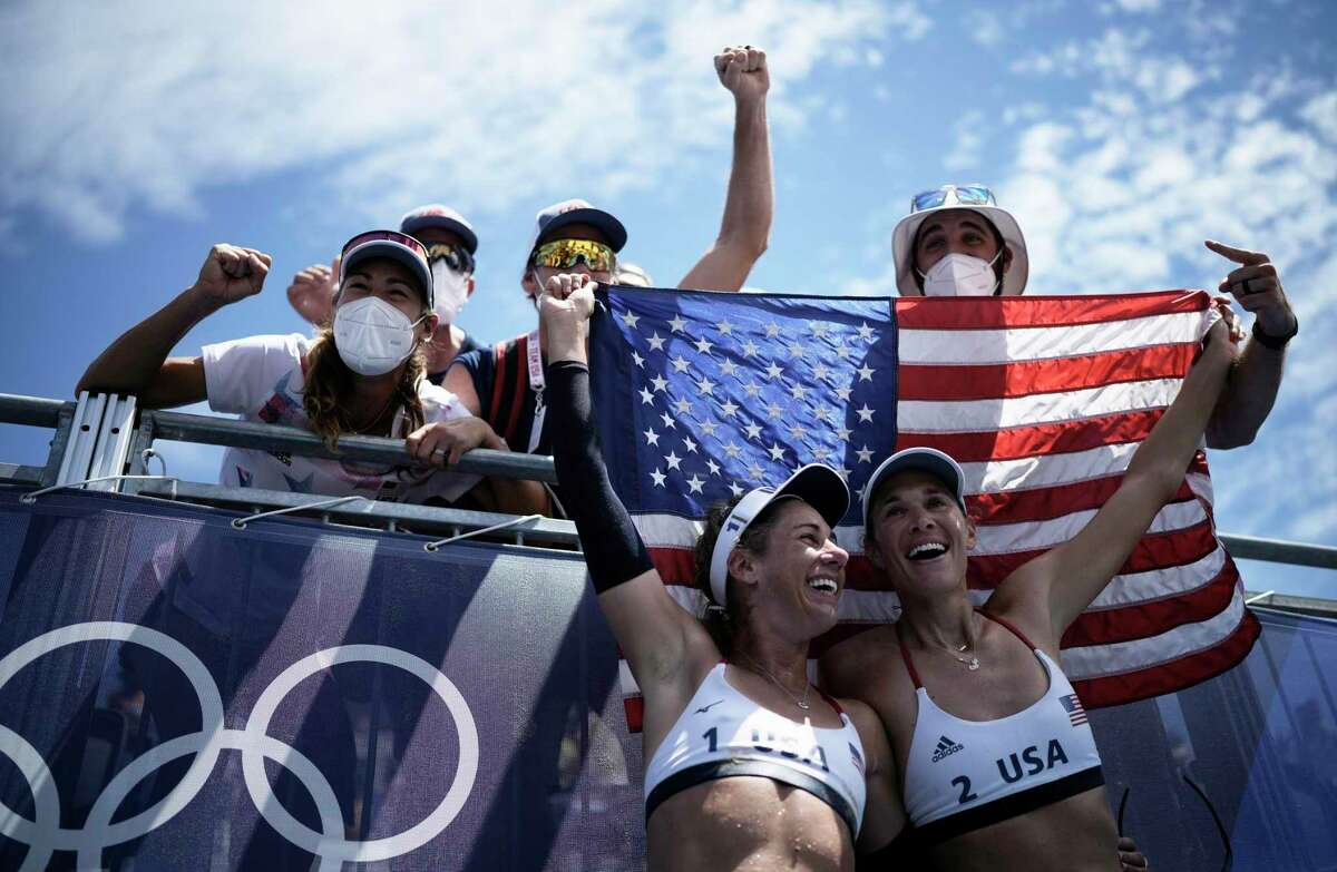 U.S. teammates April Ross (left) and Alix Klineman celebrate winning a beach volleyball gold medal match against Australia at the Summer Olympics on Aug. 6 in Tokyo.