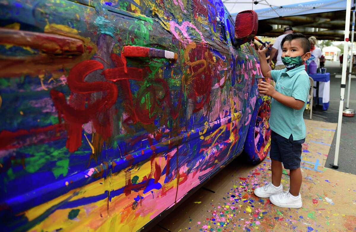 Four-year-old Stefano Angelis paints a car at the Garavel Suburu tent during The SoNo Arts Festival Saturday, August 7, 2021, in Norwalk, Conn.
