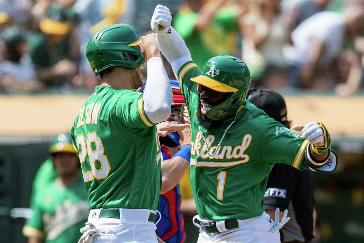 Oakland Athletics' Josh Harrison (1) celebrates with Matt Olson (28) after hitting a two-run home run against the Texas Rangers during the fifth inning of a baseball game in Oakland, Calif., Saturday, Aug. 7, 2021. (AP Photo/John Hefti)