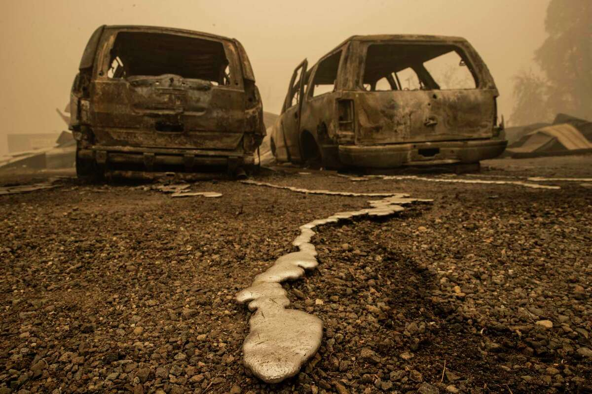 Solidified molten metal is seen behind two vehicles burned by the Dixie Fire in Greenville (Plumas County).