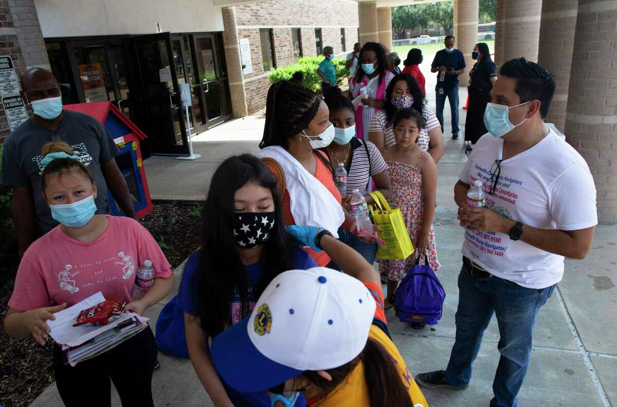 """Parents and kids wait in linet to receive vaccination shots Saturday, Aug. 7, 2021, at Bush Elementary in Houston. The City of Houston held its first """"Super Saturday"""" vaccine drives, setting up free vaccination sites at 10 schools in the area in preparation for the 2021-2022 school year. Students were offered non-COVID vaccine shots, along with COVID vaccines for eligible students."""