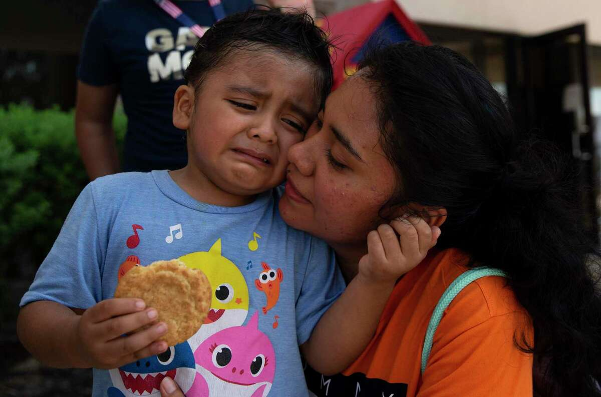 """Marcus Hernandez, 4, seeks comfort from his mother, Jennifer Gomez, after receiving a non-COVID vaccine shot at Bush Elementary in Houston. The city of Houston held its first """"Super Saturday"""" vaccine drive in preparation for the school year."""