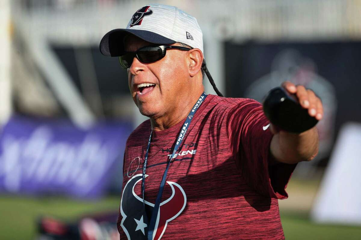 Houston Texans head coach David Culley waves at fans as his players warm up during an NFL training camp football practice Saturday, Aug. 7, 2021, in Houston.