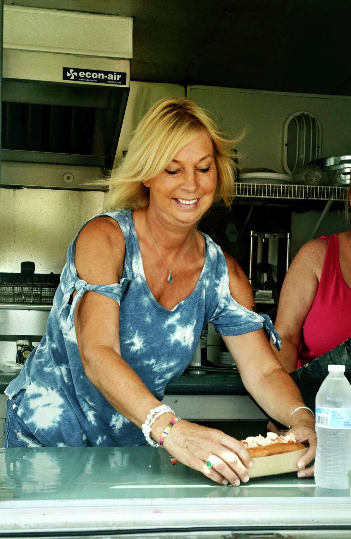 Kim Morgan makes a fresh lobster roll from her concession at Clinton Town Beach.