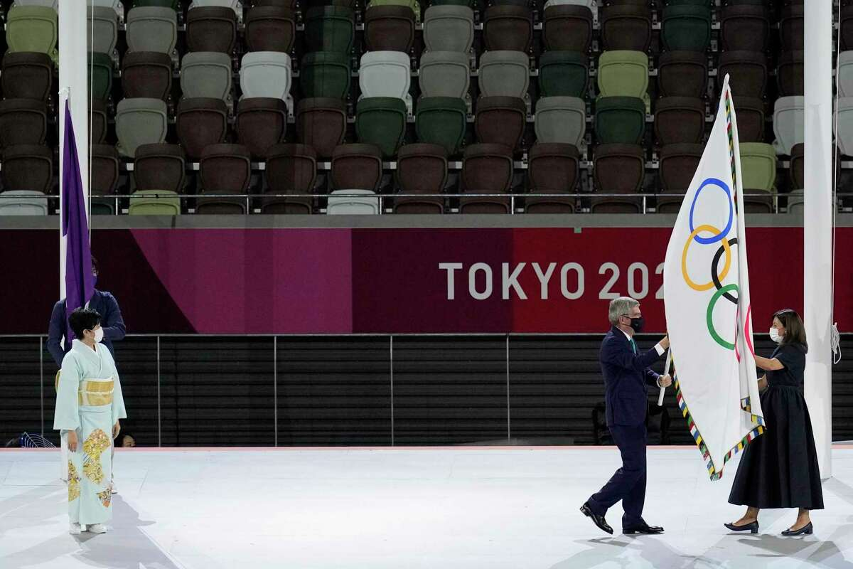 International Olympic Committee's President Thomas Bach hands over the Olympic flag to Paris mayor Anne Hidalgo, right, as Tokyo Gov. Yuriko Koike, left, looks on during the closing ceremony in the Olympic Stadium at the 2020 Summer Olympics, Sunday, Aug. 8, 2021, in Tokyo, Japan.