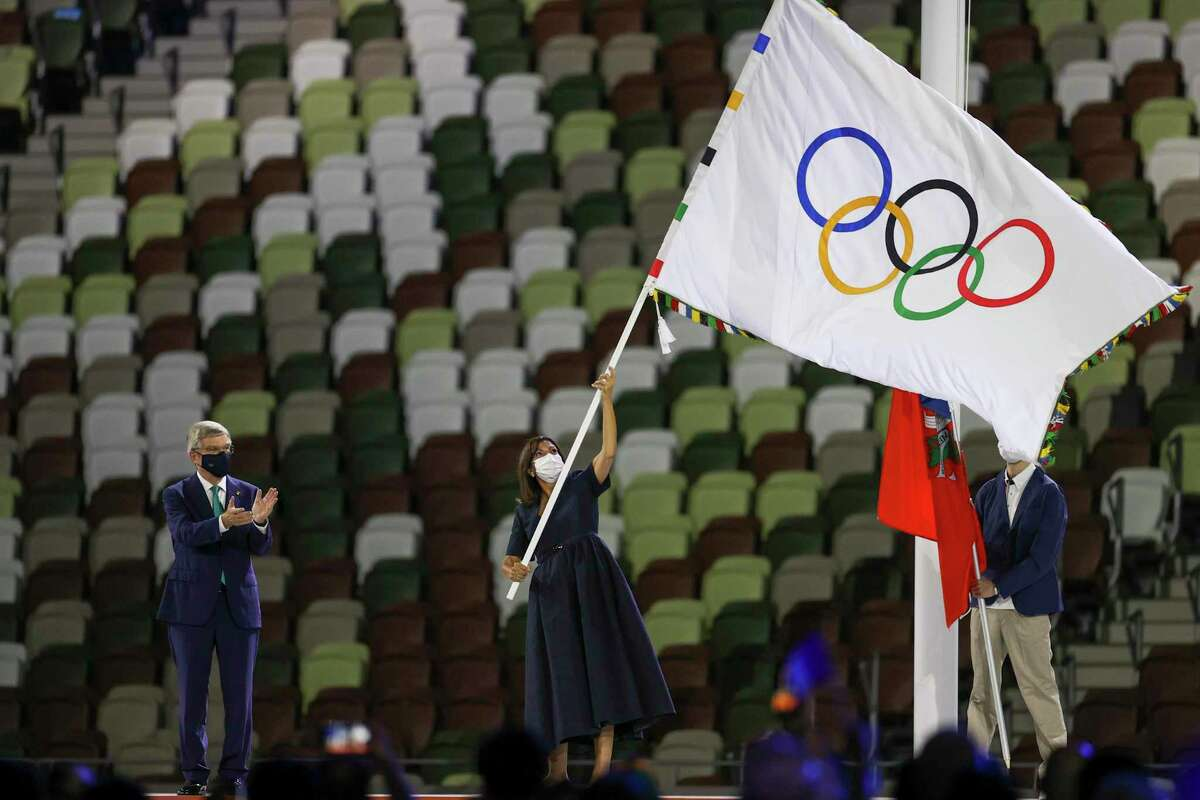 Paris Mayor Anne Hidalgo waves the Olympic flag after receiving it from International Olympic Committee's President Thomas Bach during the closing ceremony in the Olympic Stadium at the 2020 Summer Olympics, Sunday, Aug. 8, 2021, in Tokyo, Japan.