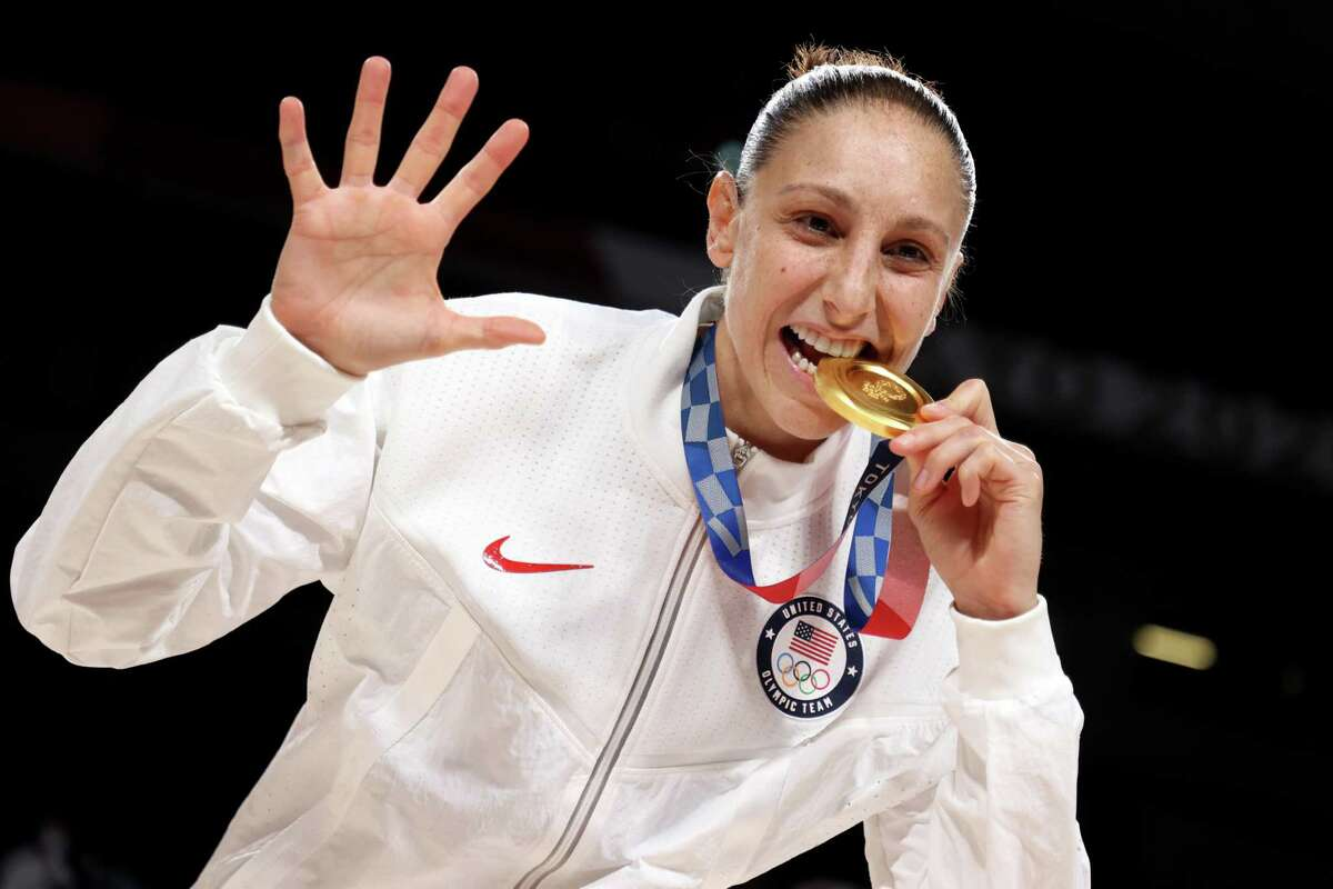 SAITAMA, JAPAN - AUGUST 08: Diana Taurasi #12 of Team United States bites her gold medal during the Women's Basketball medal ceremony on day sixteen of the 2020 Tokyo Olympic games at Saitama Super Arena on August 08, 2021 in Saitama, Japan. (Photo by Gregory Shamus/Getty Images)