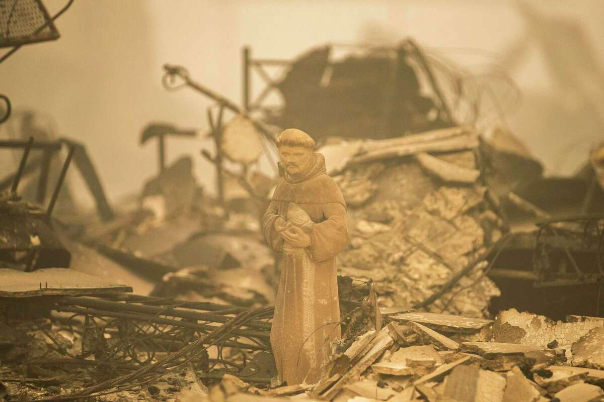 A statue of a monk stands Aug. 7 in the ruins of a property destroyed by the Dixie Fire in Greenville (Plumas County).