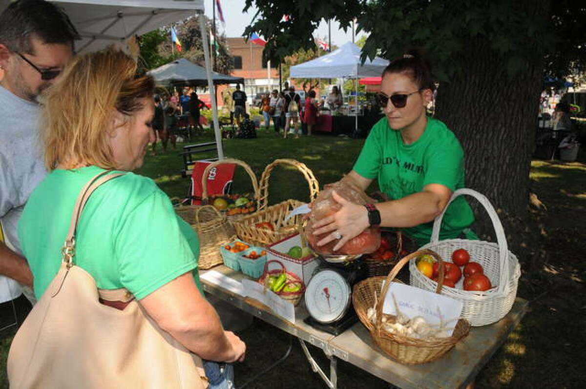 Old Six Mile Museum volunteer Kimberly Votoupal weighs tomatoes for a Melting Pot Market customer Saturday in Granite City. The markets are held the first Saturday of every month and attract about 50 vendors.