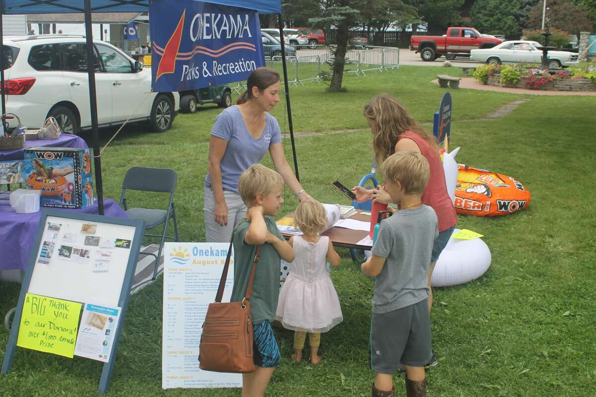 Onekama Township Parks and Recreation Committee member Michelle Ervin helps a family register for the scavenger hunt Saturday as part of the Onekama Days celebration.