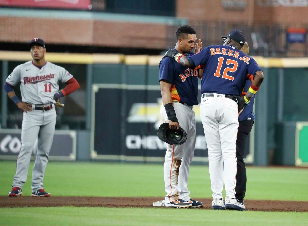 Astros manager Dusty Baker checks on Michael Brantley after he was shaken up on a collision at second base during the first inning of Sunday's game against the Twins.