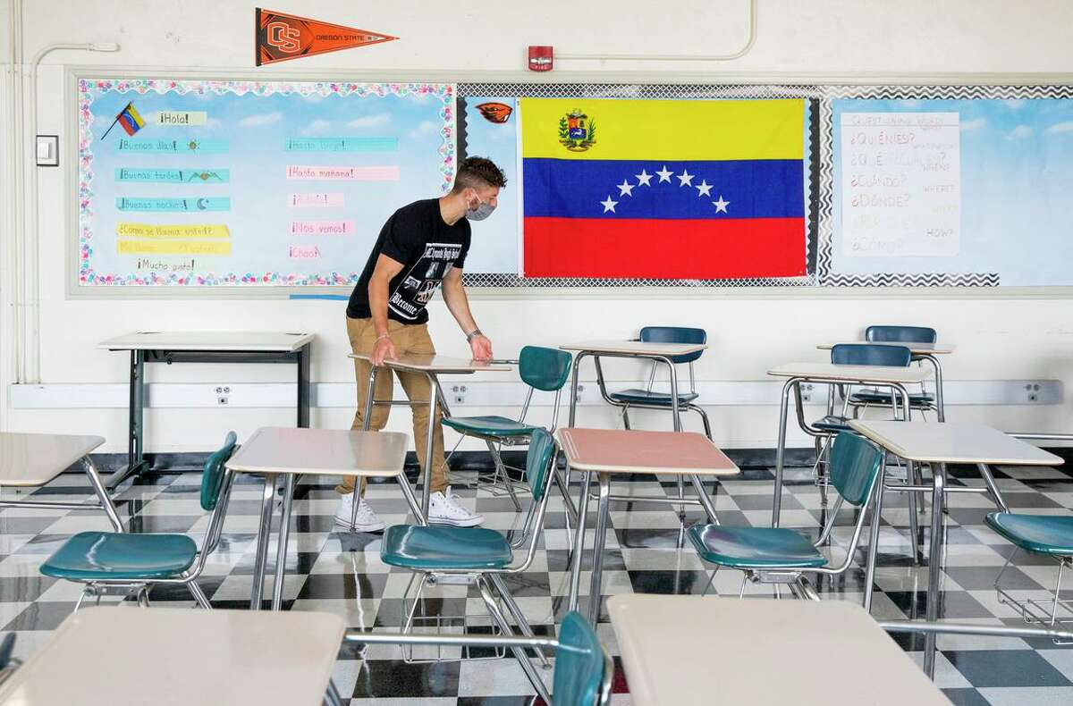Braden DeWitt arranges desks for physical distancing inside his classroom at McClymonds High School in Oakland. Bay Area schools have taken steps to address the trauma that the pandemic has caused students and their families.